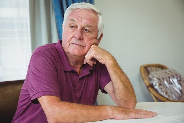 Älterer mann, der an einem tisch sitzt