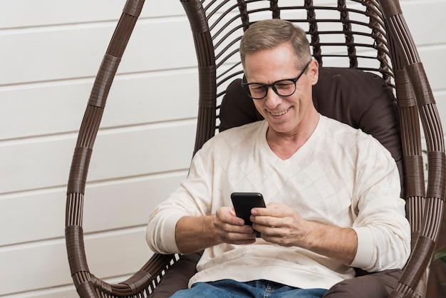 Älterer mann, der an seinem telefon schaut