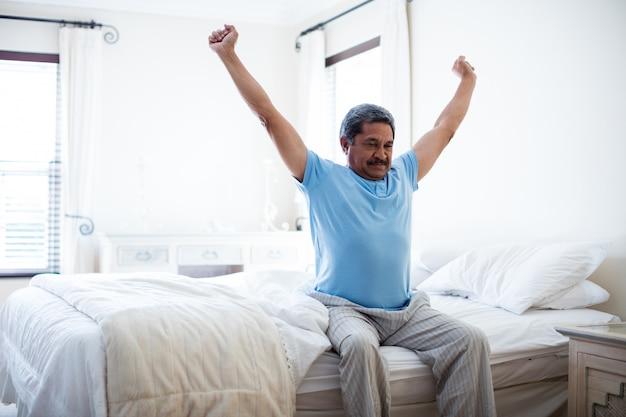 Älterer mann, der arme auf bett im schlafzimmer streckt