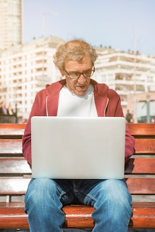 Älterer mann, der auf bank unter verwendung des laptops an draußen sitzt