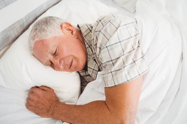 Älterer mann, der auf bett im schlafzimmer schläft