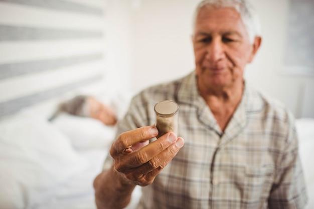 Älterer mann, der auf bett sitzt und eine tablettenfläschchen betrachtet