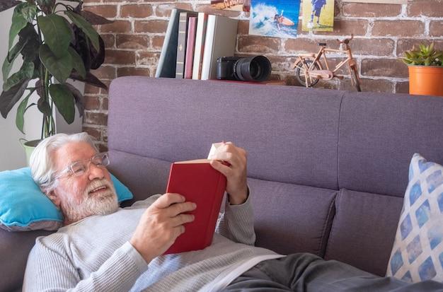 Älterer mann, der auf dem sofa liegt und zu hause ein buch liest - rentner-, freizeit- und menschenkonzept