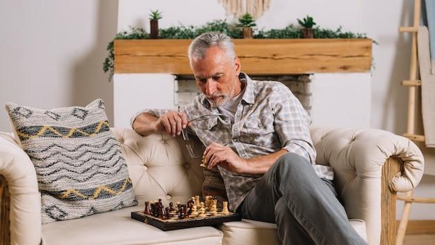 Älterer mann, der auf dem sofa zu hause spielt schach sitzt