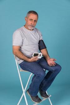 Älterer mann, der auf dem stuhl überprüft blutdruck auf elektrischem tonometer sitzt