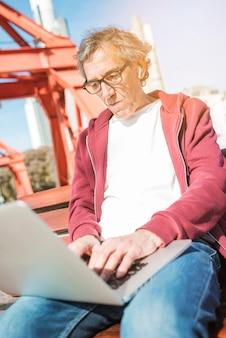 Älterer mann, der auf der bank schreibt auf laptop an draußen sitzt