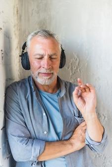 Älterer mann, der auf hörender musik der wand auf kopfhörer sich lehnt