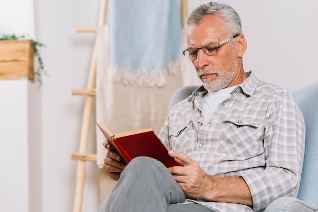 Älterer mann, der auf lehnsessellesebuch sitzt