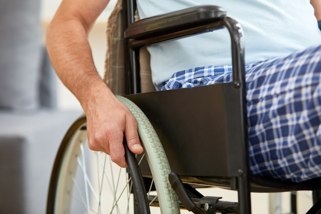 Älterer mann, der auf rollstuhl reitet