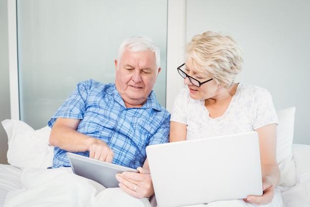 Älterer mann, der auf tablette mit frau zeigt