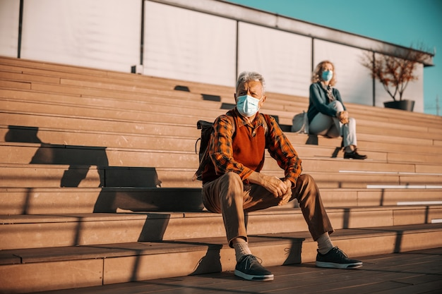 Älterer mann, der auf treppen sitzt und schützende chirurgische gesichtsmaske trägt.