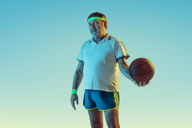 Älterer mann, der basketball auf gradientenhintergrund im neonlicht spielt. das kaukasische männliche model in guter form bleibt aktiv und sportlich.