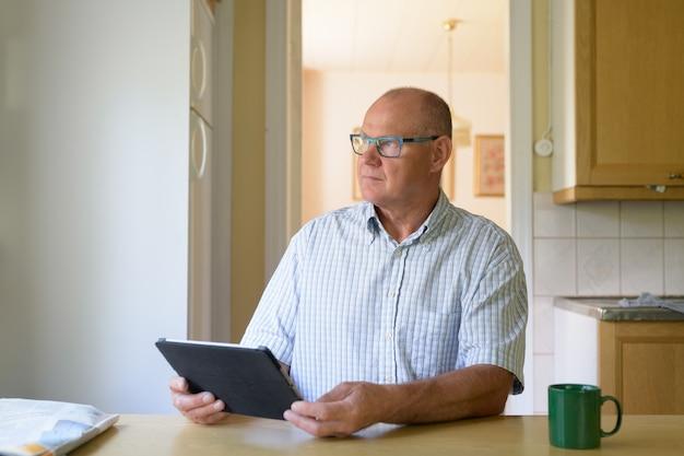 Älterer mann, der beim verwenden des digitalen tablets durch das fenster denkt