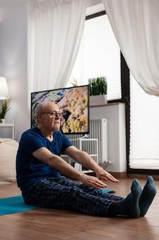 Älterer mann, der beinmuskeln ausdehnt, während er auf yogamatte im wohnzimmer sitzt