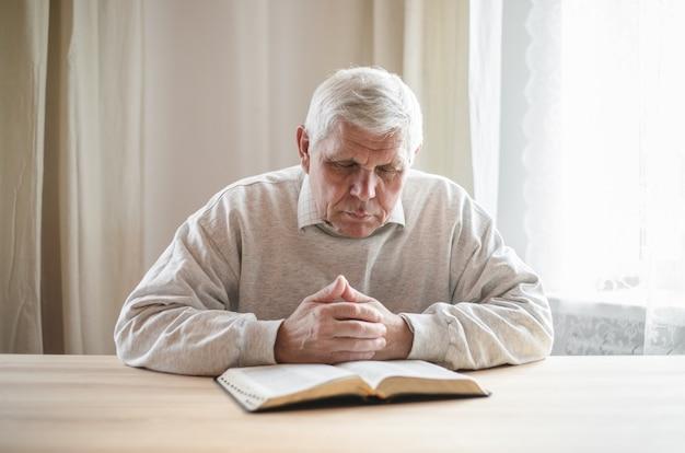 Älterer mann, der betet und eine alte bibel in seinen händen liest.