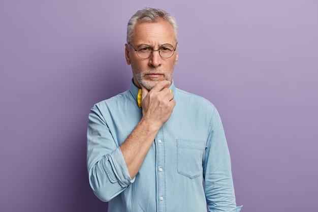 Älterer mann, der blaues hemd und gelbe fliege trägt