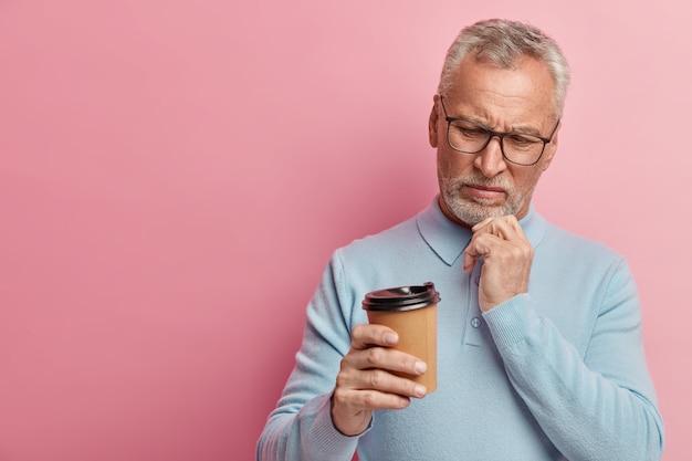 Älterer mann, der blaues hemd und trendige brillen trägt