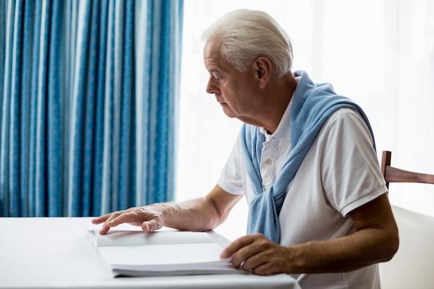 Älterer mann, der blindenschrift verwendet, um zu lesen