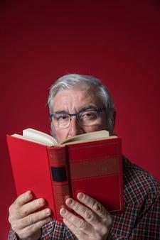 Älterer mann, der buch vor seinem gesicht gegen roten hintergrund hält