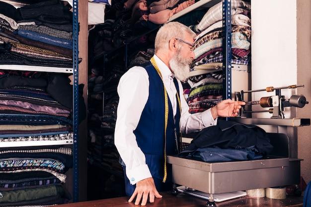 Älterer mann, der das gewebe auf maschine im shop misst