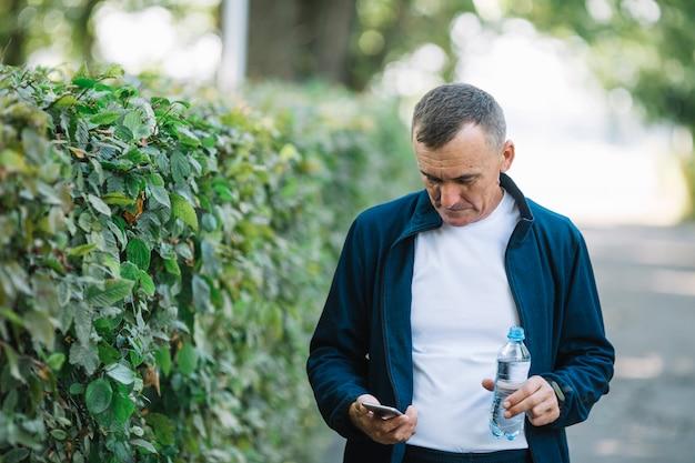 Älterer mann, der das mobile im freien überprüft
