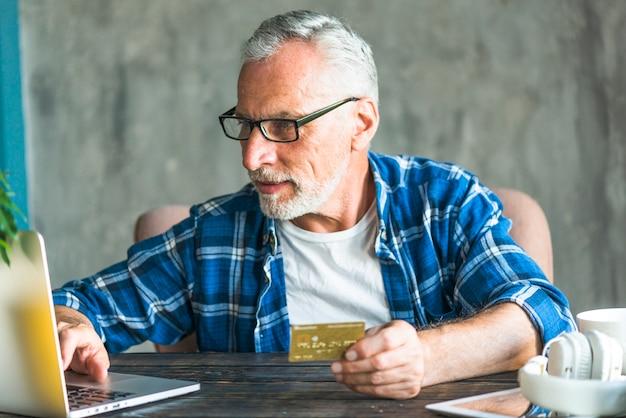 Älterer mann, der das on-line-einkaufen durch laptop tut