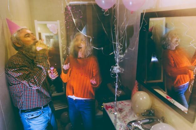 Älterer mann, der das partyhorn und die werfenden konfetti der frau in der luft auf geburtstag durchbrennt
