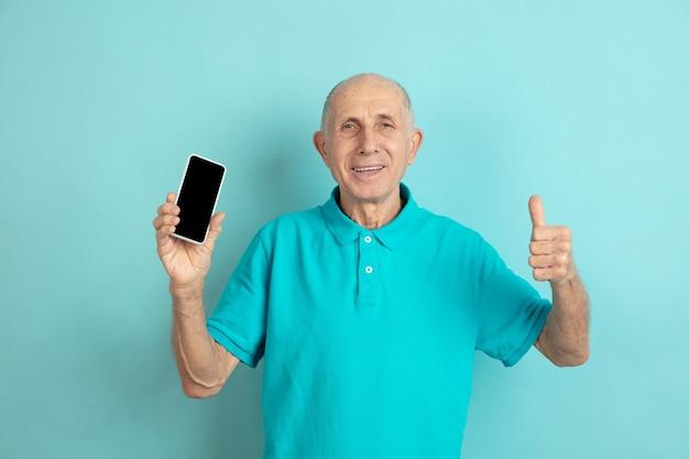 Älterer mann, der den bildschirm des leeren telefons zeigt