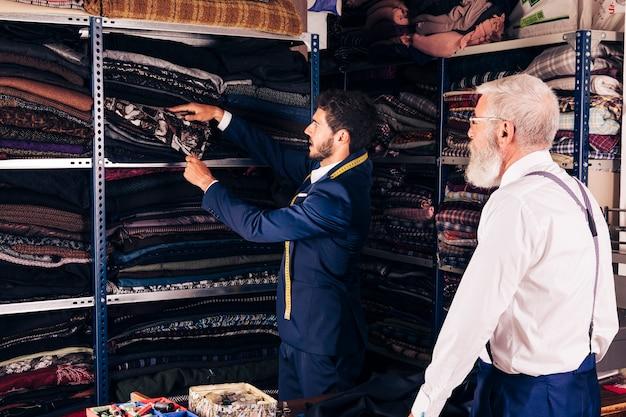 Älterer mann, der den männlichen schneider nimmt gewebe vom regal in der werkstatt betrachtet