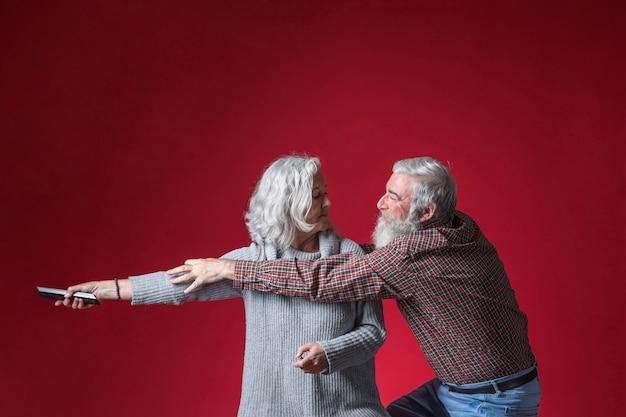 Älterer mann, der die fernbedienung von der hand seiner frau gegen roten hintergrund schnappt