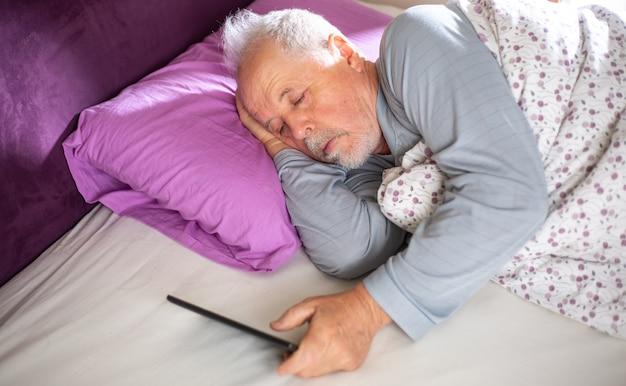 Älterer mann, der die nachrichten auf der tablette im bett am morgen, lebensstilkonzept prüft