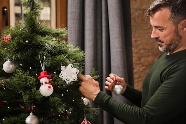 Älterer mann, der die spielwaren auf dem weihnachtsbaum vereinbart