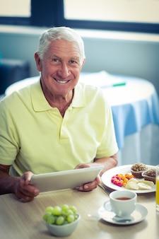 Älterer mann, der digitale tablette beim frühstücken verwendet
