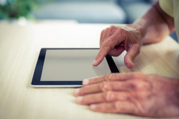 Älterer mann, der digitale tablette verwendet