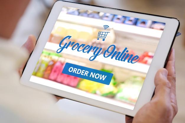 Älterer mann, der digitales tablett für onlie lebensmitteleinkauf verwendet