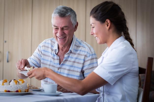 Älterer mann, der doktor im wohnzimmer kuchen gibt