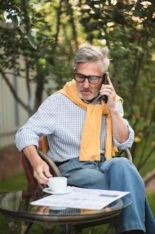 Älterer mann, der draußen am telefon spricht