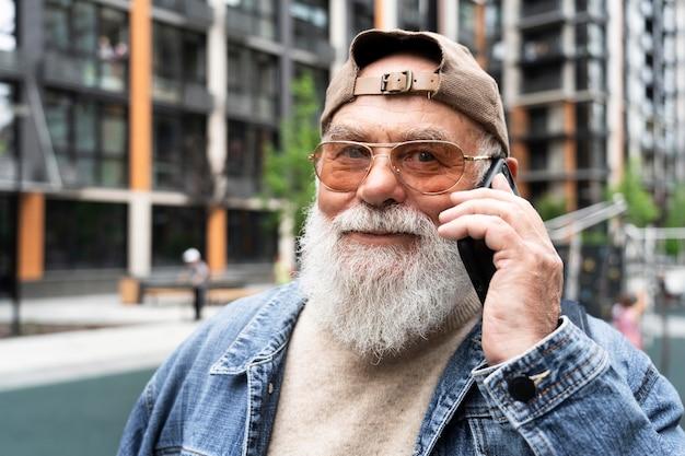 Älterer mann, der draußen in der stadt auf dem smartphone spricht