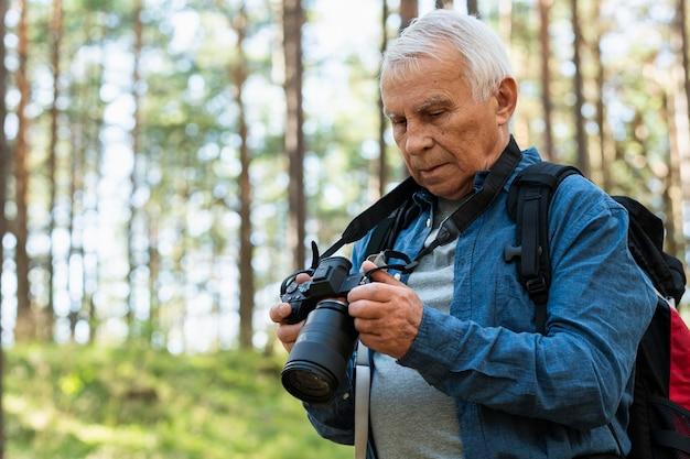 Älterer mann, der draußen mit kamera reist Kostenlose Fotos