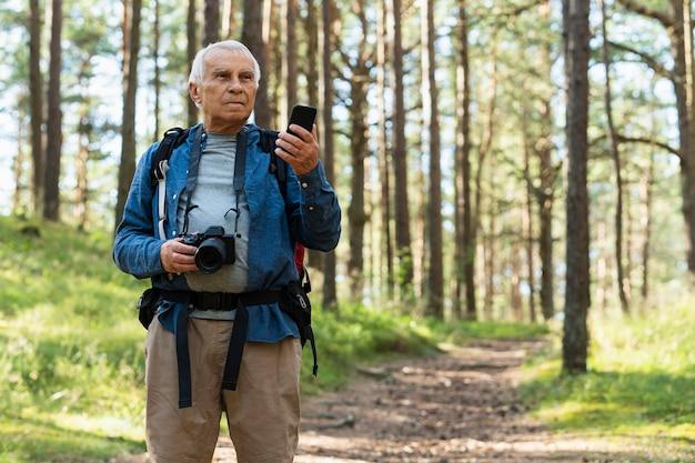 Älterer mann, der draußen mit kamera und smartphone reist