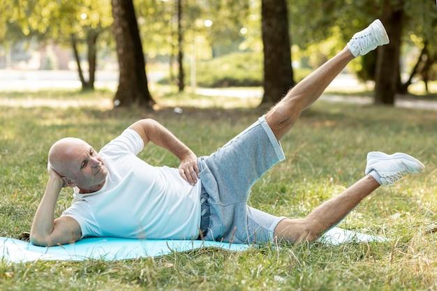 Älterer mann, der draußen übungen auf yogamatte tut