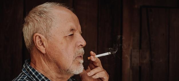 Älterer mann, der draußen zigarette raucht, die zigarettensucht, schlechte angewohnheit