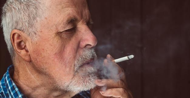 Älterer mann, der draußen zigarette raucht, die zigarettensucht, ungesundes konzept, schlechte angewohnheit