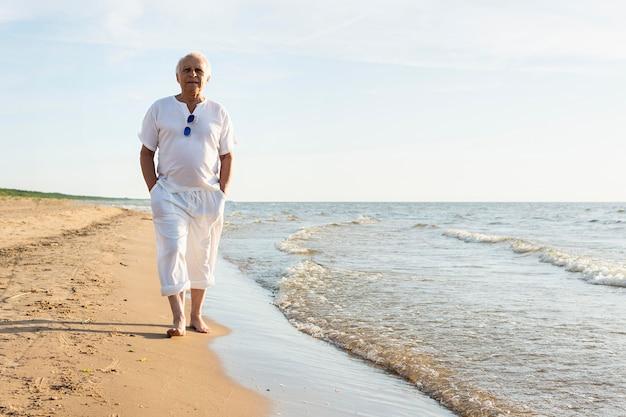 Älterer mann, der durch den strand geht, der die ansicht genießt