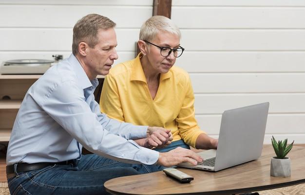 Älterer mann, der durch seinen laptop nahe bei seiner frau schaut