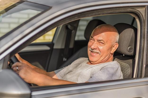 Älterer mann, der ein auto fährt und die kamera betrachtet. fahr- oder alterskonzept.