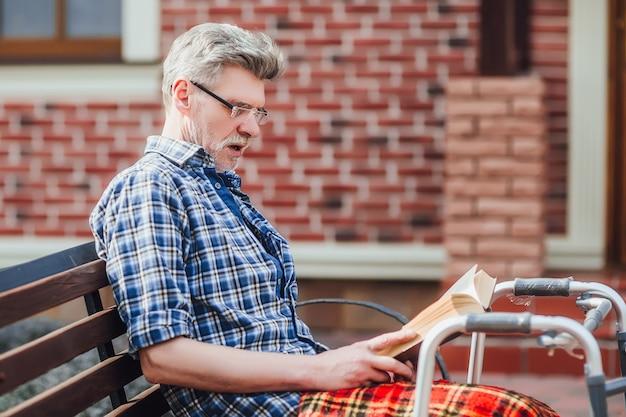 Älterer mann, der ein buch liest, während er im garten in der nähe des pflegeheims sitzt