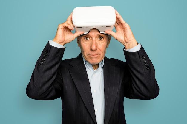 Älterer mann, der ein digitales gerät mit vr-headset trägt