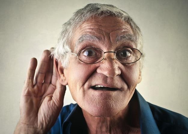 Älterer mann, der ein geheimnis hört