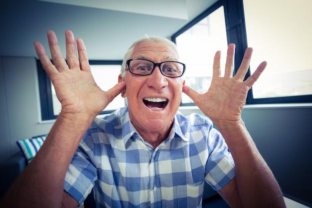Älterer mann, der ein lustiges gesicht bildet